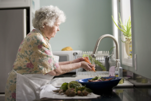elderly woman in Miami washing dishes